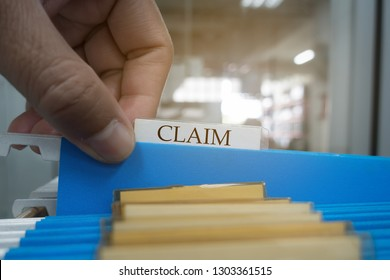 Human hand is picking up the claim document in the file for the client to the insurance company.insurance concept.