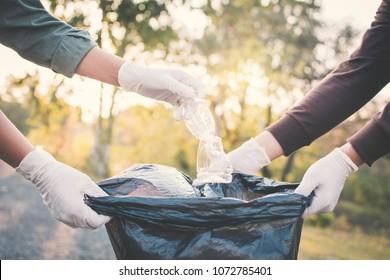 Human hand picking up plastic into bin bag on park ,volunteer concept