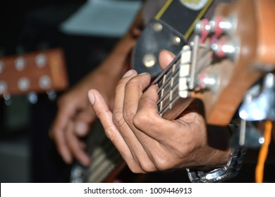 Human hand is playing guitar.