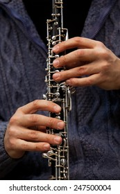 Human hand playing the oboe