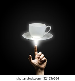 Human hand pointing with finger at cup of coffee