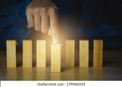 Human hand points at the front blocks wood  tor show influence and leadership, Concept business leadership for leadership teams, winners, successful people, and influential leaders.