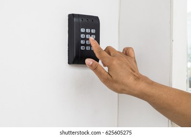 Human hand presses on the button, entering security system code. Combination PIN code on keypad. Password house alarm. Digital combination lock wall