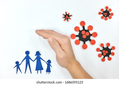 Human hand protecting a family against coronavirus paper cutout in white background. Protection and shield against covid-19 pandemic.