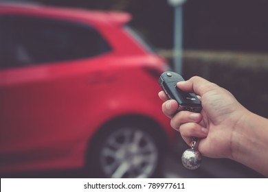 Human hand pushing button on remote control car key