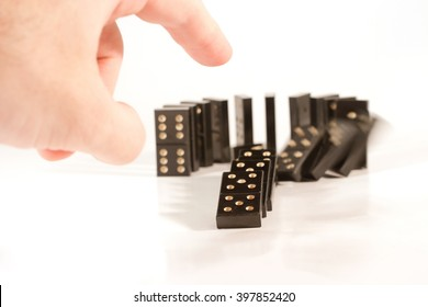 Human hand pushing a row of black dominoes (shallow DOF, selective focus on the finger and domino piece in front of the row)