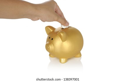 Human hand put coin into piggy bank isolated over white background