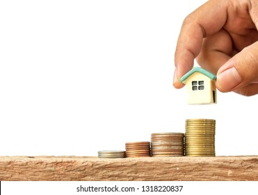 Human hand putting house model on coins stack, saving or investment for a house on white background.
