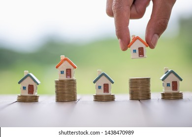 Human hand putting house model on coins stack,  planning savings money of coins to buy a home concept, mortgage and real estate investment.  saving or investment for a house.