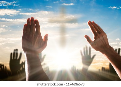 Human Hand Raising Hands With Cross In The Center Against Cloudy Sky