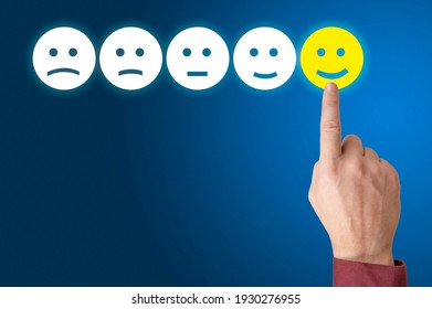 Human hand is rating with happy icon. Ranking and customer satisfaction concept. hand press on excellent smiley face rating for a satisfaction survey. blue background