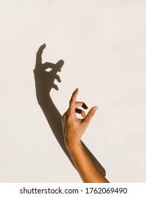 human hand shadow on vintage cream wall background.