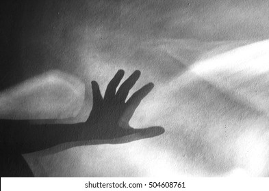 human hand shadow on vintage wall background