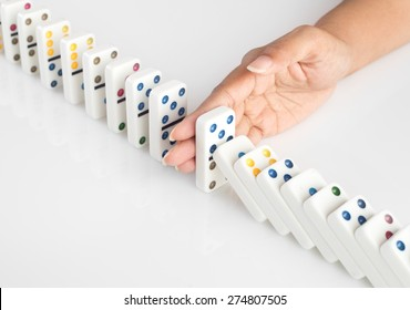 Human hand stopping a line of dominoes from falling. concept image for recovery plan and solution for cascading failures and problems. Dominoes are placed on a white table. High key image .