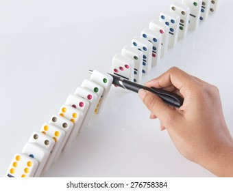 Human hand stopping a line of dominoes from falling. concept image for strategy and solution for cascading failures and problems.