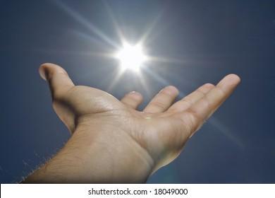 human hand, sun and blue sky
