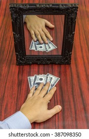 Human hand taking money from a table in front of a mirror - Shutterstock ID 387098350