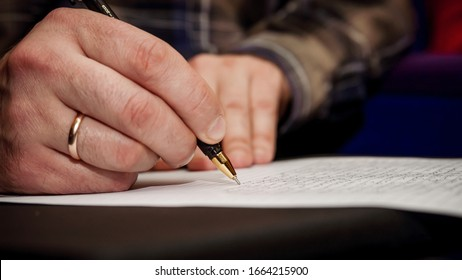 The human hand that writes text on a sheet of white paper, caligraphy