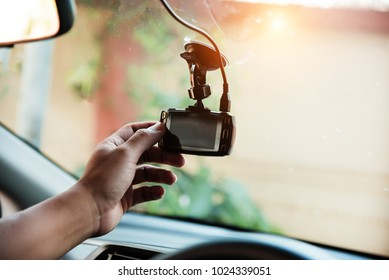 The human hand is touching camera on the car for check system of the camera recording before use,the technology for car user,for safe and secure when drive on the road.