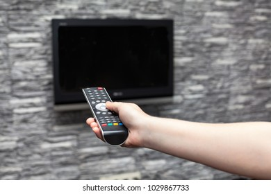 Human hand turning on flat tvset hanging on wall in a room