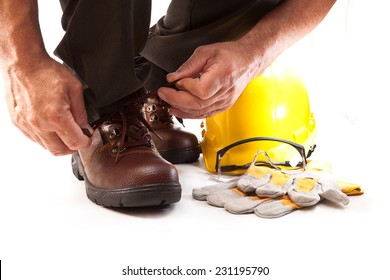 Human hand tying shoelaces on work boots, goggles, gloves and hard hat