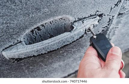 Human hand Unlocking a car door on a cold frozen winter morning
