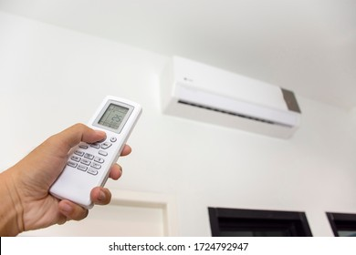 Human hand is using white remote of air conditioner for turn on and  adjust air conditioner in a room.