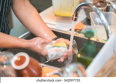Human hand washing dish or pouring glass with fresh drink water at kitchen faucet