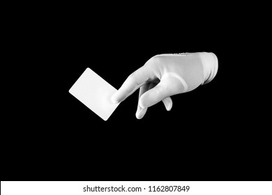 Human hand in white glove on black background. Credit card between your fingers. Gesticulation.