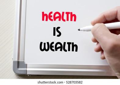 Human hand writing health is wealth on whiteboard