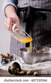Human hands adding yolk from glass plate for making cookies