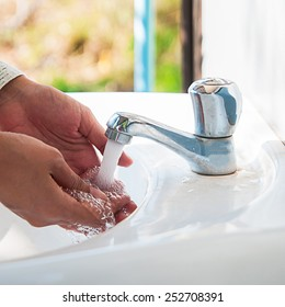human hands being washed under stream of pure water from tap