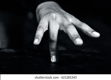 Human hands with dark black background.