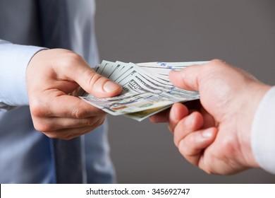 Human hands exchanging money on blue background, closeup shot
