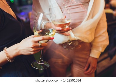 Human hands with glasses of red wine clinking them over served table.