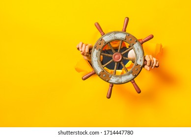 Human hands hold the ship's helm through a torn hole in a yellow paper wall. A blank space for text and information on the side.