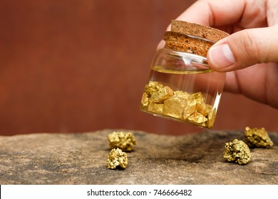 Human hands are holding bottles that contain pure gold minerals found in mines