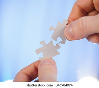 Human hands holding details of puzzle, blue background