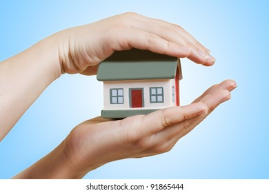 Human hands holding house model.