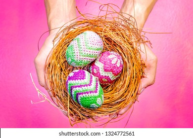 Human hands holding nest with colorful easter eggs over pink color background. Happy Easter