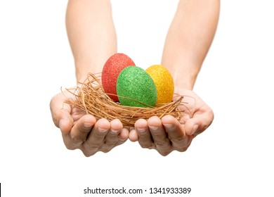 Human hands holding nest with colorful easter eggs isolated over white background. Happy Easter