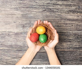 Human hands holding the nest with colorful easter eggs over wooden table background. Happy Easter
