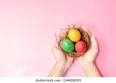 Human hands holding the nest with colorful easter eggs over pink color background. Happy Easter