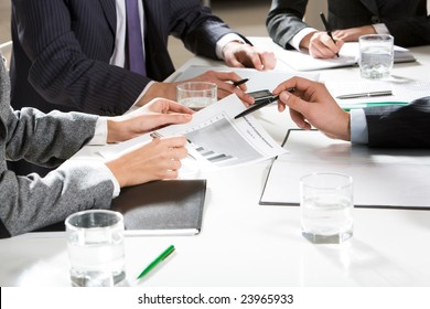 Human hands holding pens and papers, making notes in documents, touching the phone during business meeting