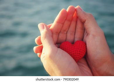 Human hands holding red crochet heart and blur sea background, Love concept, Valentine's Day, Vintage style