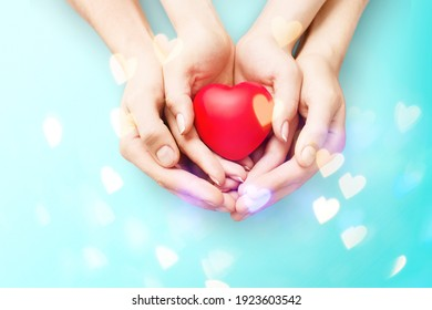Human hands holding red toy heart. Valentine's Day