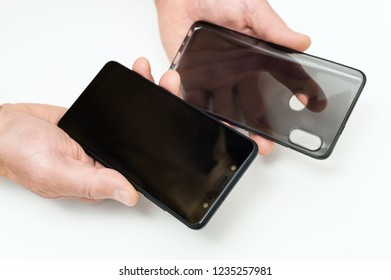 Human hands are holding a smartphone and a silicone case.