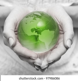 Human hands holding and take care about green planet .