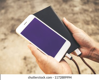Human hands holding white smartphone charging battery from external power bank in outdoor