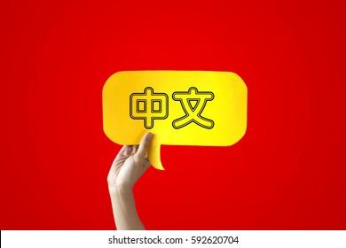 Human Hands Holding 'Zhongwen' Yellow Speech Bubble Over Red Background - Zhongwen means Chinese language